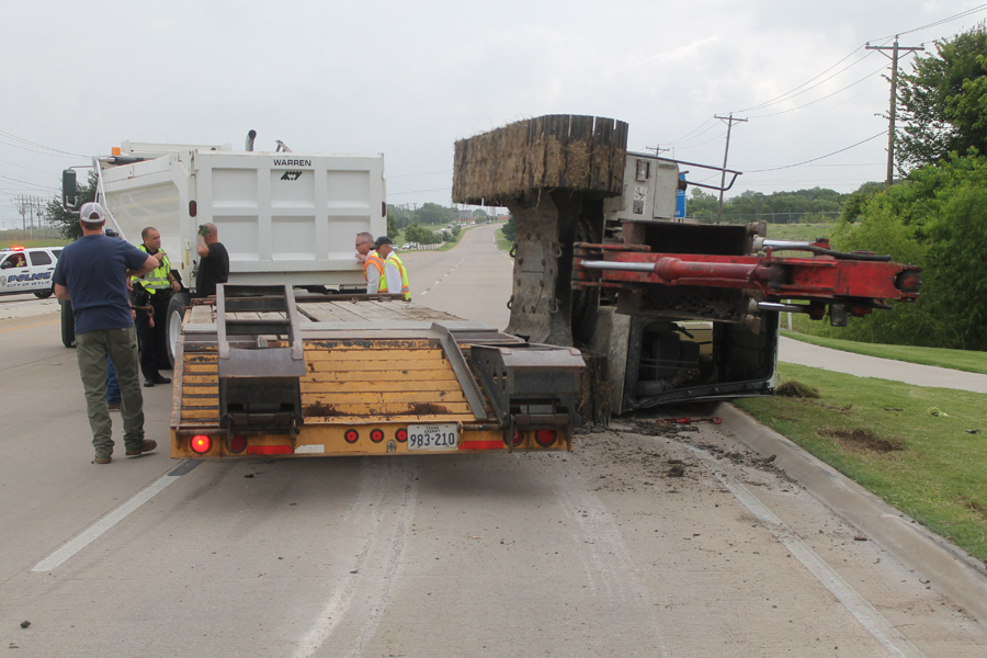 Track hoe topples off trailer