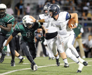 Wylie East quarterback Braden Shewmake stiff-arms a Poteet defender while trying to get downfield.