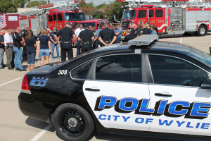 Wylie policemen and firefighters bow their heads in prayer during a brief ceremony in remembrance of Harris County Deputy Sheriff Darren Goforth who was gunned down last month. Ceremonies were held at the First Baptist Church parking front parking lot and Wylie High School bus loop at 11 a.m. Friday, a time designated for emergency vehicles throughout the country to flash their lights for a minute of remembrance.