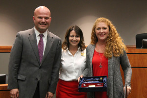 Heather Leggett, shown center, was named the new Wylie ISD Board of Trustees president during the Nov. 16 meeting. Standing with Leggett is outgoing President Barbara Goss, holding a photo and gavel she received in gratitude for her service, and Superintendent David Vinson.