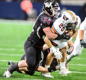 Oladipo Awowale/The Wylie News Taylor Green wraps up Frisco Wakeland running back Cole Starnes during last Saturday's bi-district action at AT&T Stadium. The Pirates return to the same venue this Saturday for a 9 p.m. area-round game with Rockwall Heath.