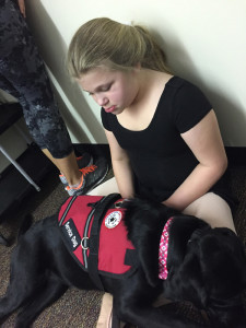 Ava Robertson sits with her service dog Minaj at ballet practice.