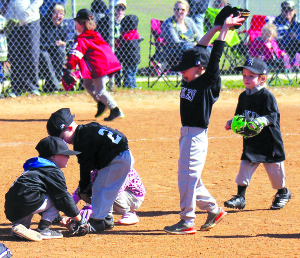 Members of the Rockies' 4U T-Ball team race to the ball during a Saturday morning contest with the Diamond Divas as part of opening day for the Wylie Baseball League, which took place on a chilly, windy day at Community Park.