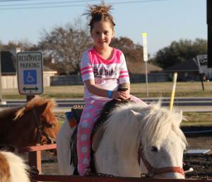 Sydney Bradford sits atop a pony at the Birmingham Elementary School Carnival.