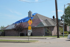 Roofers work to clean up the mess left behind following the hail storm late Monday.