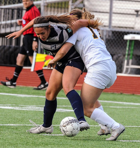 Evan Ghormley/The Wylie News Wylie East's Jordyn Perry and Forney's Caitlynne Smith (17) lock up, literally, as each tries to control the ball during last week's area-round game in Rockwall. The Lady Raiders scored in the final minutes to produce a 1-0 victory.