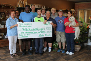 The Wylie Downtown Merchants Association presented a $1,000 check to the Wylie/Sachse/Murphy Area Special Olympics last week. The funds were raised at the merchants' Wylie 500 Pedal Race Races held May 1. Pictured, front l-r, Lynn Grimes, Special Olympian Wilson Izker, Special Olympian Cole Wells, Coach Marty Smith, Mike Carroll, Pam Wells and MAK; back l-r, Alice Stewart, Bobby Heath, Danny Wells and WDMA Secretary Janice Martz. WDMA has donated $12,000 over the 12 years the race has been held.