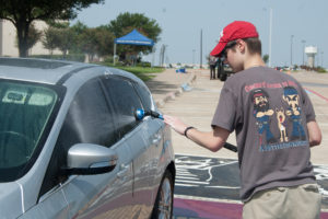 Tyler Lamarre makes sure to remove all dirt and grime from a car he washes during the Wylie P.O.L.I.C.E. Club car wash Saturday, July 16. The fundraiser monies will benefit the families of fallen DPD officers.