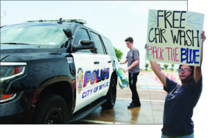 Noah Stagg of the Wylie P.O.L.I.C.E Club washes a patrol vehicle Saturday July16. The club, under the supervision of Officer Michael Stewart, held a car wash fundraiser. All donations received will benefit the families of fallen officers. Right, Samantha Wong advertises the car wash the old fashioned way.