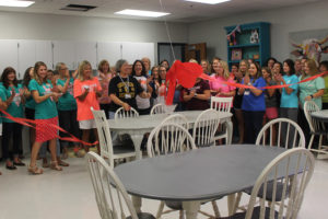PTA members and teachers clap as Melinda Sarles, Tibbals Elementary Principal, cuts the ribbon to the newly renovated teacher's lounge Thursday, Aug. 18.