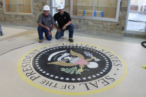 The presidential seal is prominently featured at the entrance to George W. Bush Elementary School in Wylie, set to open with the fall school term. Showing off the seal inlay are, l-r, Cliff Claussen and Ricky Smith of Gallagher Construction Services, construction manager for Wylie Independent School District.