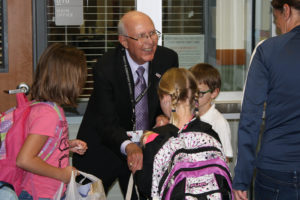 Don Whitt, namesake of Whitt Elementary, hands out stickers as students walk through the first doors for the first day of school early Monday morning.