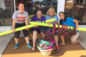 Friends have fun with a set of giant knitting needles at Fiber Circle.