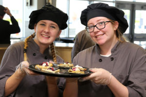 Students Haley Smalley (WEHS) and Meredith Wright (WHS) serve up some tasty treats at the grand opening of Cafe 544 Sept.21.
