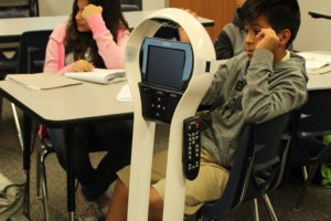 A homebound Wylie student can get the benefit of a live lecture from Draper Intermediate School mathematics teacher Kelsey Biasatti through use of one of three special robots.  A special mobile robot with audio / visual feeds, sits in a classroom as a stand-in for a homebound Wylie student.