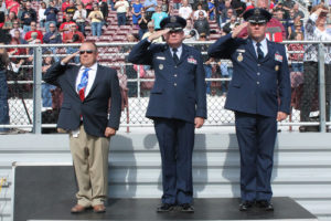 Returning the salute as Wylie Air Force JROTC cadets pass in review during the Veterans Day tribute at Wylie Stadium are school board trustee Lance Goff, a United States Marine Corps veteran, Col. Steve Jones and Col. Brooks McFarland.